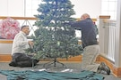 Steven R. Balderrama, left, and Brian Waterman right, both operations specialists of Directorate of Plans, Training, Mobilization and Security, arrange one of two holiday trees used to light up the lobby of Fort Riley's garrison command building Nov. 21. The lobby was decorated with holiday ornaments, an electric fireplace and other festive decor for a visit with Santa following the Holiday Tree Lighting Ceremony Dec. 1 at Ware Parade Field at 500 Huebner Road.