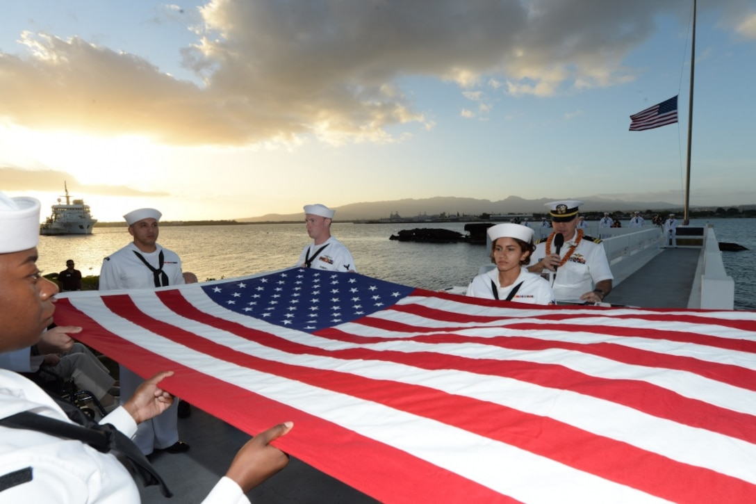 Sailors fold a large American flag during a commemoration ceremony.
