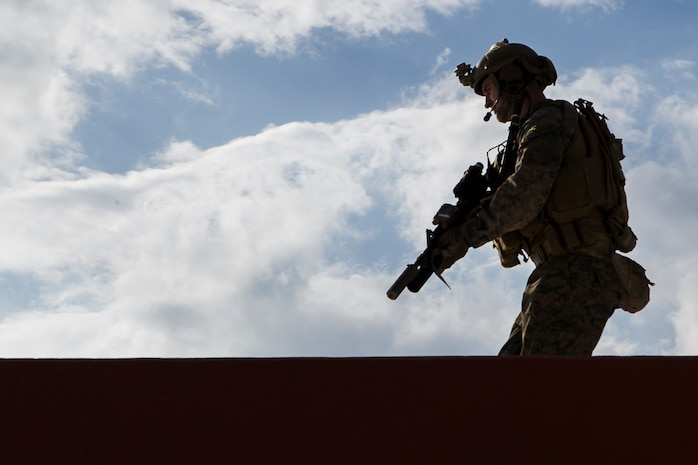 Sgt. Benjamin Deweese, a reconnaissance team leader with the 31st Marine Expeditionary Unit's Maritime Raid Force, moves atop a mock embassy during Marine Expeditionary Unit Exercise at Camp Hansen, Okinawa, Japan, Dec. 5, 2017.