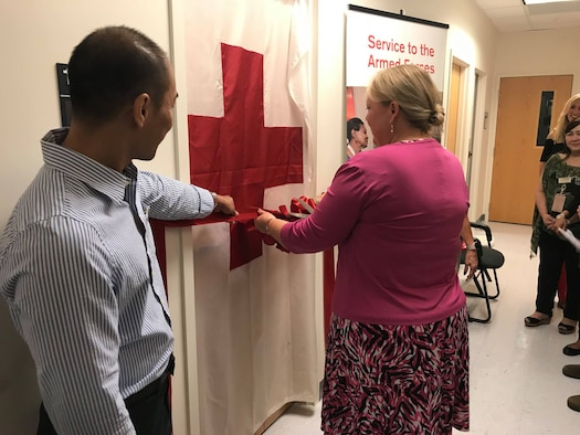 Mrs. Lynae Cox, wife of Brig. Gen. Douglas Cox, 36th Wing commander, cuts the ribbon during the official opening of the new Red Cross service office Dec. 6, 2017, at Andersen Air Force Base, Guam. The office marks the first time in 20 years that the Red Cross provided on-bases services to service members. (U.S. Air Force photo by Airman 1st Class Christopher Quail)