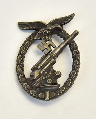 "Plans call for this artifact to be displayed near the B-17F Memphis Belle™ as part of the new strategic bombardment exhibit in the WWII Gallery, which opens to the public on May 17, 2018. Luftwaffe (German Air Force) antiaircraft gunner uniform badge.  Bomber crews faced deadly antiaircraft, or ""flak,"" defenses."