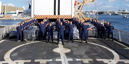 Members of the Coast Guard Cutter Escanaba crew stand next to approximately 12.4 tons of cocaine Dec. 7, 2017