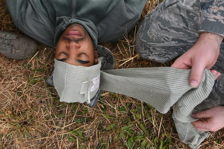 U.S. Air Force Senior Airman Nelson Blackshear, 20th Civil Engineer Squadron administrative journeyman, lies on the ground as his head is bandaged during self-aid buddy care (SABC) training at Poinsett Electronic Combat Range near Wedgefield, S.C., Dec. 5, 2017.