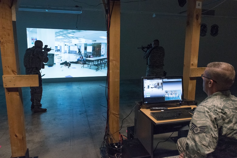 Staff Sgt. Patrick Dulzo, 934th Security Forces Assistant Unit Training Manager monitors Staff Sgt. Robert Smolen and Staff Sgt. Richard Sapp, 934th SF Fireteam members, as they maneuver through a scenario using the Multiple Interactive Learning Objectives simulator at the Minneapolis-St. Paul Air Reserve Station, Minn. on Dec. 3, 2017. The MILO system provides defenders with the ability to customize scenarios to meet qualification and operational goals and requirements. (U.S. Air Force photo by Master Sgt. Eric Amidon)