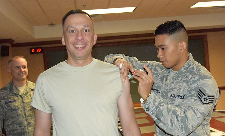 Staff Sgt. Tam Nguyen, 78th Medical Group Immunization Clinic noncommissioned officer in charge, administers a flu shot to Col. Lyle Drew, 78th Air Base Wing commander. The Influenza vaccine is here and available for all TRICARE beneficiaries. The goal is to have 90 percent of the active duty and Reserve population vaccinated by Dec. 15. Group commanders and first sergeants will coordinate with the immunization clinic to schedule a point of distribution to administer the vaccine within their groups. There is no need to schedule an appointment, walk-ins are accepted in the immunization clinic, Mondays through Fridays from 7:30 a.m. to 4:30 p.m. (U.S. Air Force photo/RAYMOND CRAYTON, JR.)