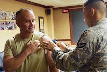 Staff Sgt. Tam Nguyen, 78th Medical Group Immunization Clinic noncommissioned officer in charge, administers a flu shot to Chief Master Sergeant Emilio Hernandez, 78th ABW command chief. The Influenza vaccine is here and available for all TRICARE beneficiaries. The goal is to have 90 percent of the active duty and Reserve population vaccinated by Dec. 15. Group commanders and first sergeants will coordinate with the immunization clinic to schedule a point of distribution to administer the vaccine within their groups. There is no need to schedule an appointment, walk-ins are accepted in the immunization clinic, Mondays through Fridays from 7:30 a.m. to 4:30 p.m. (U.S. Air Force photo/RAYMOND CRAYTON, JR.)