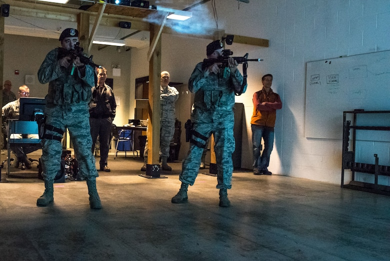Staff Sgt. Robert Smolen and Staff Sgt. Richard Sapp, 934th Security Forces Fireteam members, engage targets during an exhibition run of the Multiple Interactive Learning Objectives simulator for the honorary commanders program at the Minneapolis-St. Paul Air Reserve Station, Minn. on Dec. 3, 2017. The MILO system prepares defenders for upcoming qualifying exams and deployment scenarios. (U.S. Air Force photo by Master Sgt. Eric Amidon)