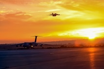 An Air Force C-5M Super Galaxy from the 22nd Airlift Squadron lands as a C-17 Globemaster III takes off at Marine Corps Air Station Miramar, Calif., Nov. 18, 2017. The aircraft delivered equipment and personnel to Argentina to help in the search for the Argentina Navy submarine ARA San Juan. (U.S. Air Force photo by Staff Sgt. Nicole Leidholm)