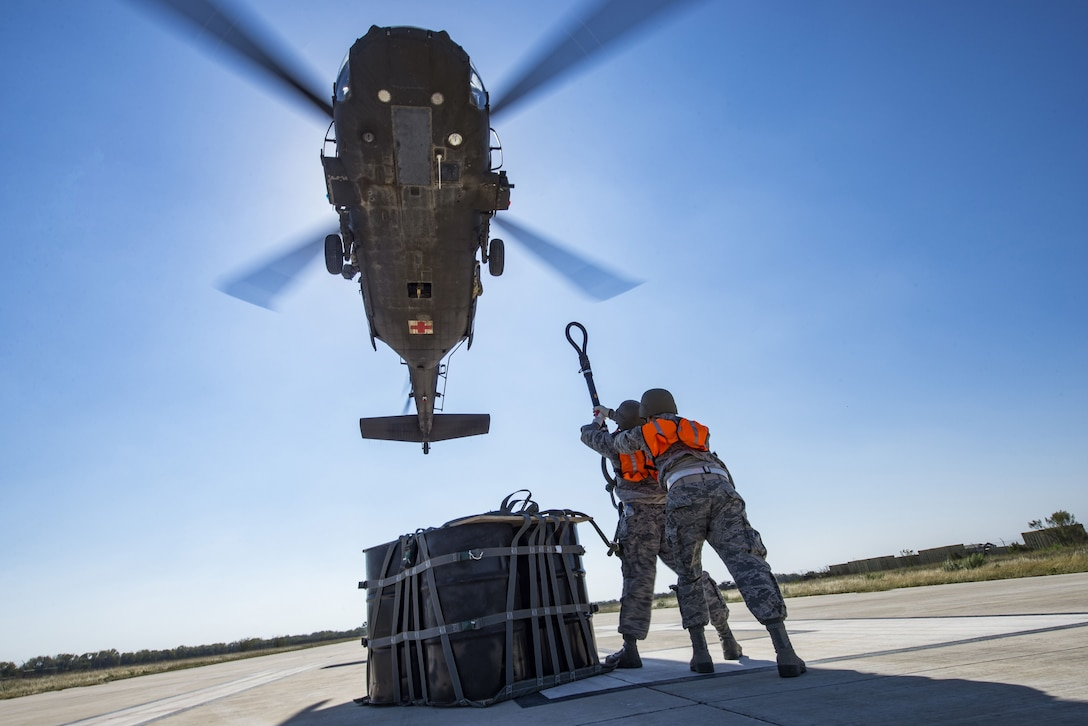 Airmen from the 26th Aerial Port Squadron attach a cargo bag with 2,000 pounds of relief supplies to the hook of a UH-60 Black Hawk helicopter flown by Texas Army National Guard Soldiers during Operation Alamo Evacuation at Martindale Army Airfield, Texas, Nov. 18, 2017. Approximately 36,000 pounds of cargo and 27 passengers were transported as part of the sling load and medical evacuation exercise. (U.S. Air Force photo by Senior Airman Stormy Archer)
