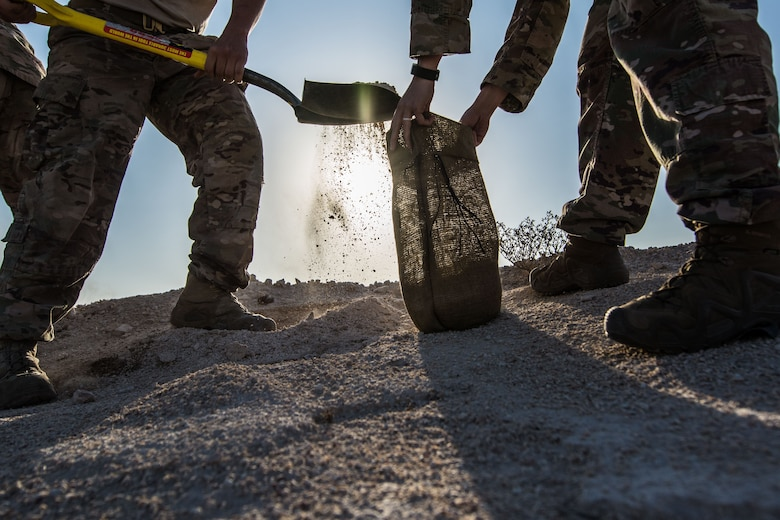 Airmen assigned to the 379th Expeditionary Civil Engineer Squadron fill sand bags during a joint chemical threat training exercise, Nov. 25, 2017, at Al Udeid Air Base, Qatar. The sandbags were used to secure munitions while explosive ordnance disposal technicians were assessing them. (U.S. Air National Guard photo by Staff Sgt. Patrick Evenson)