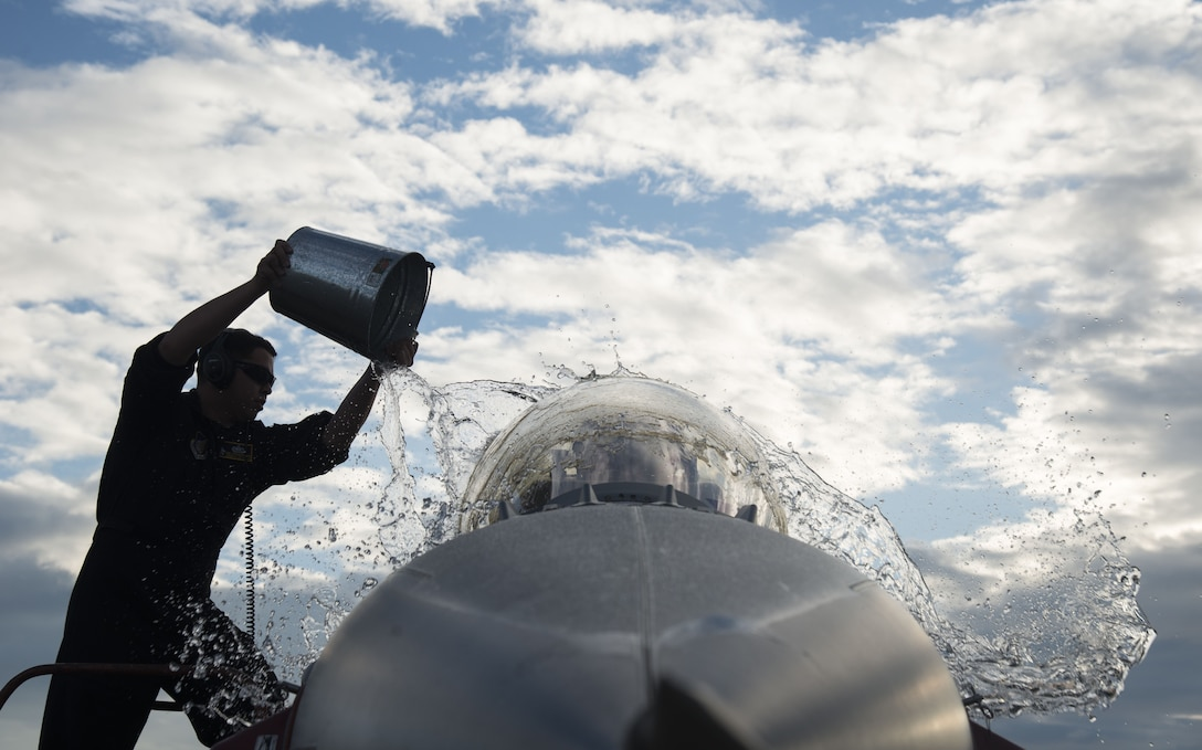 Staff Sgt. Steven Pedrick, Pacific Air Forces F-16 Demonstration Team crew chief, throws water on an F-16 Fighting Falcon at Japan Air Self-Defense Force Nyutabaru Air Base, Japan, Nov. 29, 2017. The PACAF F-16 Demonstration Team promotes positive relations between the U.S. and nations across the Indo-Asia-Pacific region. (U.S. Air Force photo by Senior Airman Brittany A. Chase)