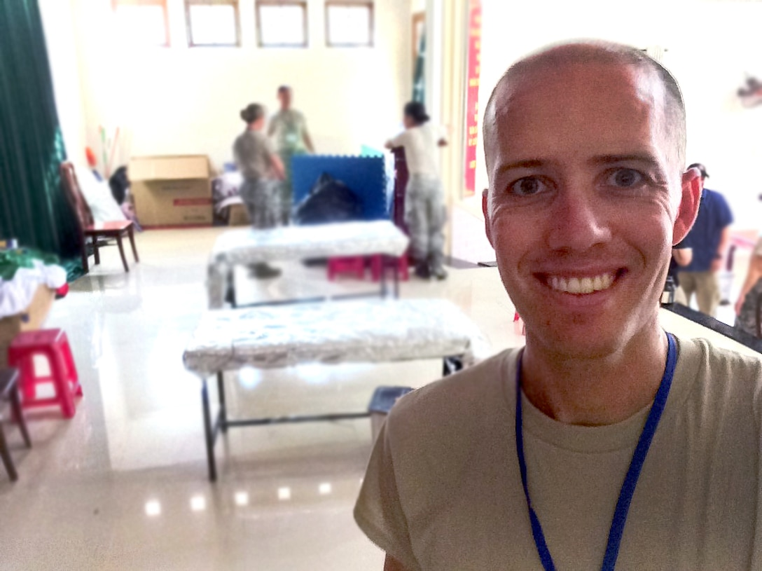 Maj. (Dr.) Cody Butler, 78th Medical Group clinical medicine flight commander, poses in the makeshift clinic set up in the government community center in Tam Ky, Quang Nam Province, Vietnam. Butler, a physical therapist, was in Vietnam as part of a team seeing patients and building relationships with local physicians during the humanitarian assistance engagement Operation Pacific Angel Vietnam 2017. (U.S. Air Force photo)