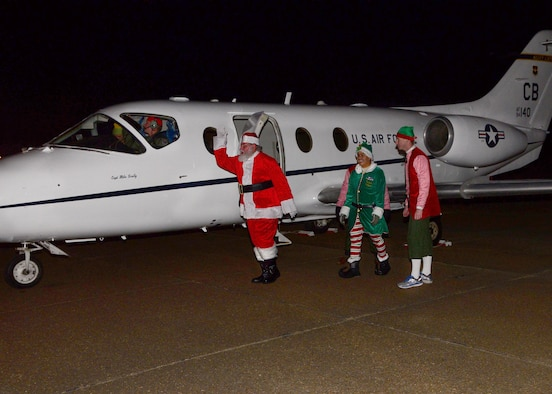 Santa Claus and three of his elves exit a T-1A Jayhawk, piloted by Capts. Christian Litscher, 14th Operations Group Commander's Action Group, and Michael Lewis, 48th Flying Training Squadron Chief Programmer, Dec. 6, 2017, on Columbus Air Force Base, Mississippi. Santa then hopped on a fire truck from the 14th Civil Engineer Squadron and led the way to the Chapel Annex where members of Team BLAZE lit the base's Christmas tree. (U.S. Air Force photo by Airman 1st Class Beaux Hebert)