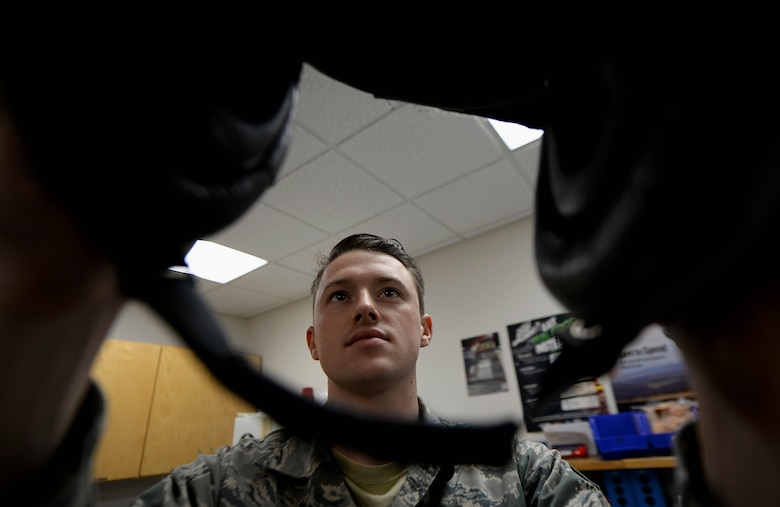Senior Airman Hayden Harrison, 48th Flying Training Wing Aircrew Flight Equipment technician, inspects a helmet's visor Dec. 5, 2017, on Columbus Air Force Base, Mississippi. At Columbus AFB, AFE Airmen do not have to learn how to sew together parachutes or pilots' G-suits, but do have to learn how to fix hundreds of helmets, harnesses and survival kits every year. (U.S. Air Force photo by Airman 1st Class Keith Holcomb)