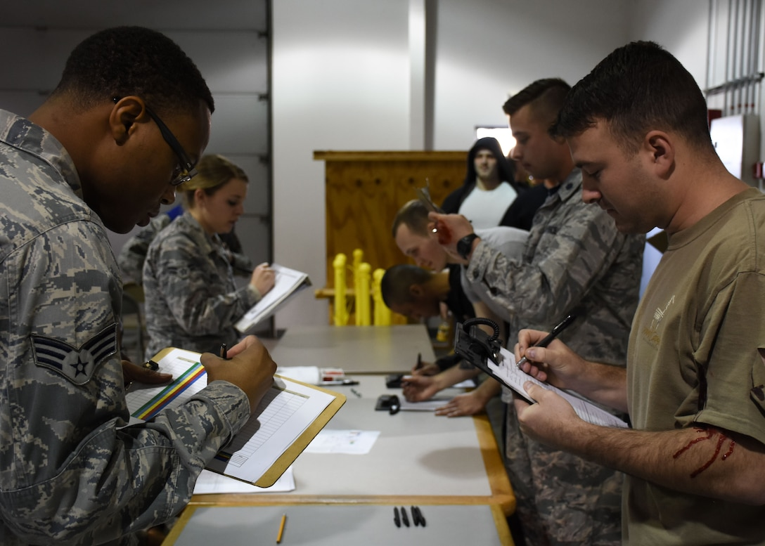 Members of the patient administration team and volunteers simulating flu symptoms complete screening forms during a total force point of distribution (POD) exercise at Whiteman Air Force Base, Mo., Dec. 2, 2017.