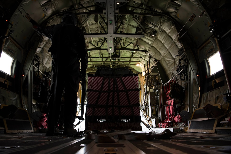 U.S. Air Force Staff Sgt. Kellan Hyacinthe, 37th Airlift Squadron C-130J Super Hercules loadmaster, prepares cargo wrapped in Christmas wrapping paper to be dropped out the back of a U.S. Air Force C-130J for Operation Toy Drop 2017 over Alzey Drop Zone, Germany, Dec. 6, 2017. The operation was designed to improve interoperability with NATO allies. (U.S. Air Force photo by Senior Airman Devin M. Rumbaugh)