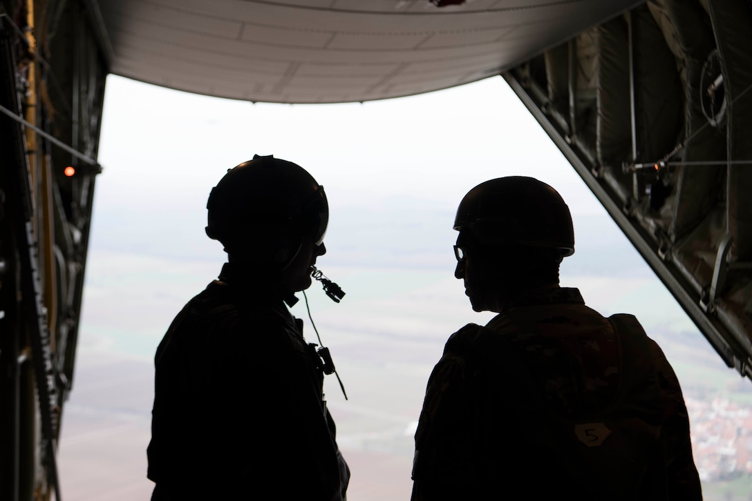 U.S. Air Force Master Sgt. Cecil Johnson, 37th Airlift Squadron C-130J Super Hercules loadmaster, speaks with a U.S. Army jumpmaster in a U.S. Air Force C-130J over Alzey Drop Zone, Germany Dec. 6, 2017. Paratroopers with the U.S. Air Force, U.S. Army, German, Italian, Dutch, British, and Estonian militaries participated in Operation Toy Drop 2017 to maintain their military free fall and jumpmaster proficiencies. (U.S. Air Force photo by Senior Airman Devin M. Rumbaugh)