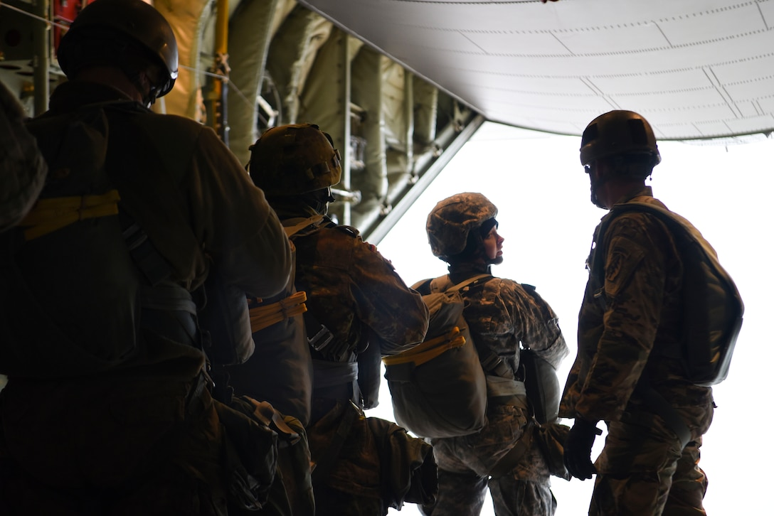 A U.S. Army paratrooper speaks to the U.S. Army jumpmaster prior to jumping out of the U.S. Air Force C-130J Super Hercules over Alzey Drop Zone, Germany, Dec. 6, 2017. The paratroopers performed static-line jumps out of the aircraft as a part of Operation Toy Drop 2017. (U.S. Air Force photo by Senior Airman Devin M. Rumbaugh)