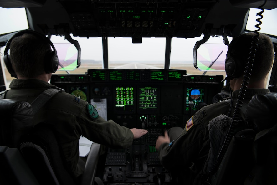 U.S. Air Force Capt. Jared Johnson (left) and U.S. Air Force 1st Lt. Kyle Holzem, both C-130J Super Hercules pilots assigned to the 37th Airlift Squadron, take off for Operation Toy Drop 2017, in a U.S. Air Force C-130J on Ramstein Air Base, Germany, Dec. 6, 2017. The aircraft flew over Alzey Drop Zone, Germany, where paratroopers from the U.S. Army, U.S. Air Force, German, Italian, Dutch, British, and Estonian militaries performed static-line jumps out of the aircraft. (U.S. Air Force photo by Senior Airman Devin M. Rumbaugh)