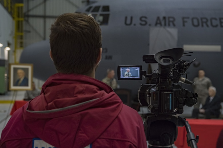 """A local news reporter records a speech given by U.S. Army Maj. Gen. James Hoyer, the Adjutant General of the West Virginia National Guard, at a C-130H plane naming ceremony Dec. 7, 2017 at McLaughlin Air National Guard Base, Charleston, W.Va. The aircraft was given the name """"The General Mac"""" to honor Brig. Gen. (ret) James K. McLaughlin, who founded the West Virginia Air National Guard and was a pilot in World War II with the famous Eight Air Force. (U.S. Air National Guard photo by Airman Caleb Vance)"""