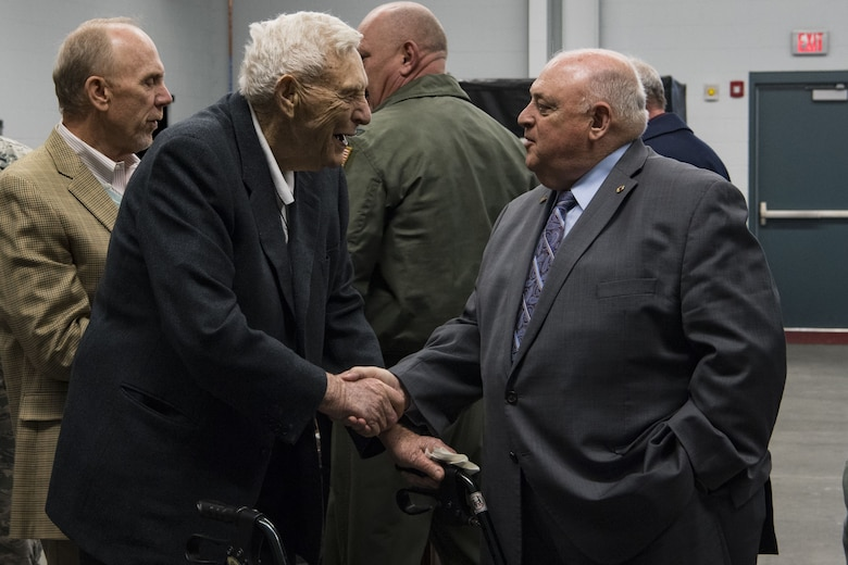 """Retired U.S. Air Force Brig. Gen. J. Kemp McLaughlin shakes the hand of Retired U.S. Army Maj. Gen. Allen Tackett at a C-130H plane naming ceremony Dec. 7, 2017 at McLaughlin Air National Guard Base, Charleston, W.Va. The aircraft was given the name """"The General Mac"""" to honor McLaughlin, who founded the West Virginia Air National Guard and was a pilot in World War II with the famous Eight Air Force. (U.S. Air National Guard photo by Airman Caleb Vance)"""