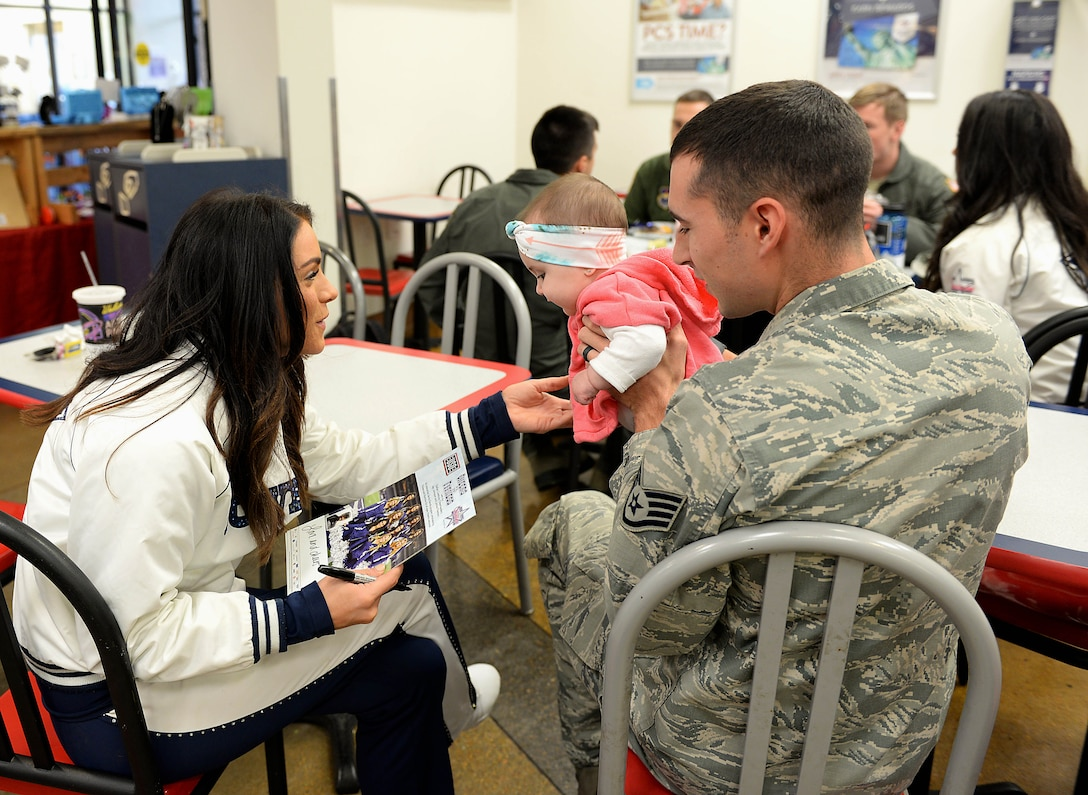 Staff Sgt. Zachary Kunkler, 14th Security Forces Squadron Military Working Dog handler, and his daughter, Emrie, speak with Kelsey, Dallas Cowboys Cheerleader, Dec. 4, 2017, at the Exchange on Columbus Air Force Base, Mississippi. The cheerleaders met with Airmen and their families throughout the day. (U.S. Air Force photo by Airman 1st Class Keith Holcomb)