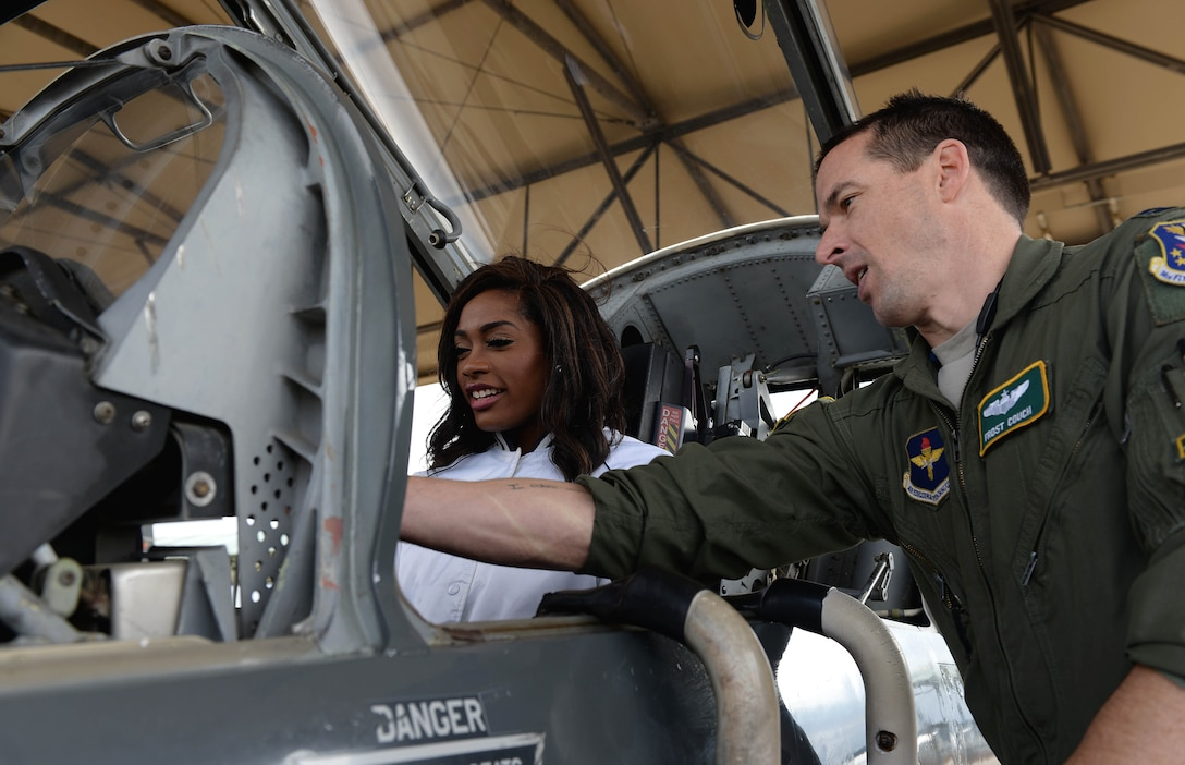 Khalyn, Dallas Cowboys Cheerleader, sits inside a T-38C Talon as Capt. James Couch, 49th Fighter Training Squadron Assistant Upgrading Instructor Pilot Flight Commander, talks about some of the key features during a tour of the flight line on Columbus Air Force Base Mississippi, Dec. 4, 2017. Numerous members of the cheerleading squad visited the base where they were shown the 14th Flying Training Wing mission and conducted a Cheer to Fitness Clinic for children at the Youth Center. (U.S. Air Force photo by Airman 1st Class Keith Holcomb)