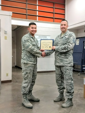 Airman 1st Class Kirstan Lin, 49th Civil Engineer Squadron Heating, Ventilation and Air Conditioning apprentice, receives the June Top III Airman Award from Master Sgt. Timothy Gatten, 54th Aircraft Maintenance Squadron first sergeant and Top III president, Nov. 28, 2017, at Holloman Air Force Base, N.M. During the month of October, Lin responded to emergency calls concerning inoperative cooling equipment at the Next-Generation Radar Weather Forecast Operations building. He repaired critical air conditioning systems restoring cooling to a $2 million radar providing weather coverage for 48,000 square miles and 800,000 people. His efforts allowed forecasting to resume enabling weather coverage for the local area leading to 5,312 flying operations and 656 training hours.