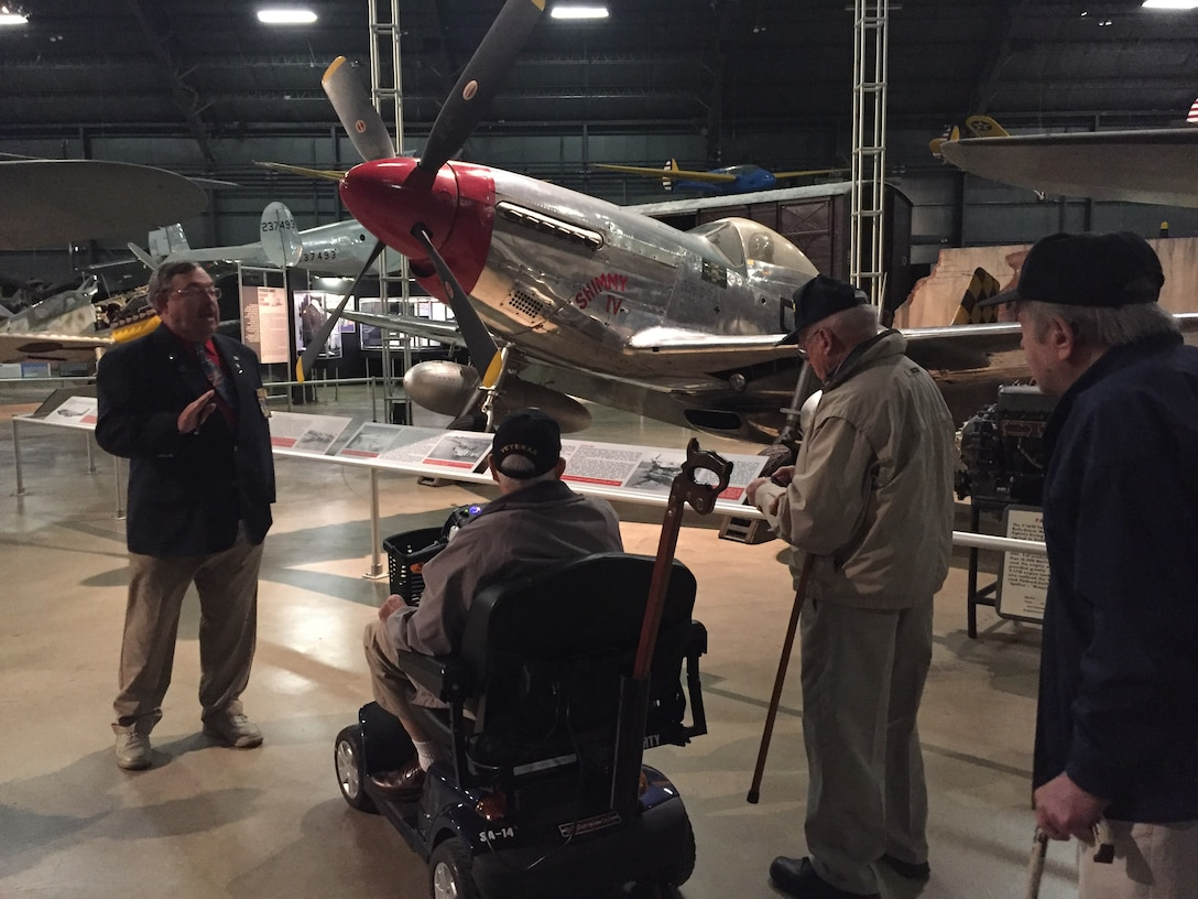 Wendell Miller, a docent at the National Museum of the U.S.Air Force, imparts facts about the North American P-51D Mustang fighter in the World War II Gallery to members of the Honoring Our Promises group Dec. 1. Eighteen area veterans enjoyed a tour and lunch, among them Larry Reynolds,WWII Army combat medic and liberator ofJewish concentration camp Gunskirchen Lager, on scooter; Air Force veteran Les Mills of Middletown; and William Wilmer, retired Air Force pilot.(Skywrighter photo/Amy Rollins)