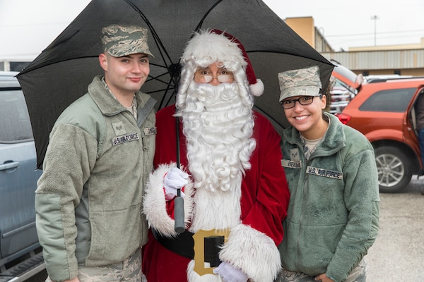Members of the Joint Base San Antonio-Lackland community pose for a photo with Santa at JBSA-Lackland during the Trees for Troops program Dec. 7, 2017.