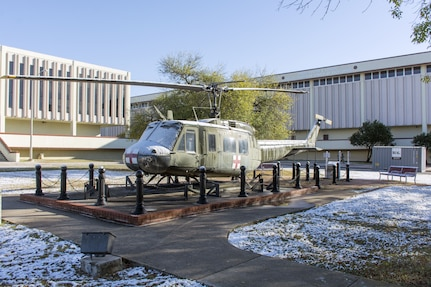 The UH-1 helicopter on display at the U.S. Army Medical Department Center and School partially covered in snow. Thursday's event was the earliest seasonal snowfall on record for San Antonio.