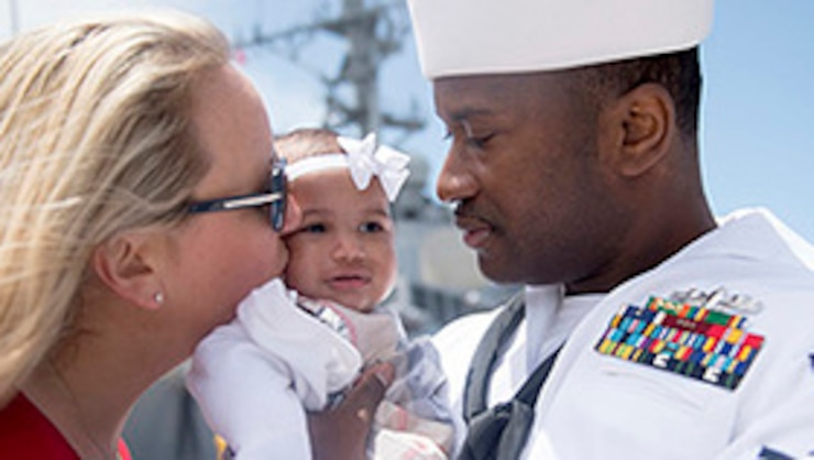 A sailor holds his newborn daughter
