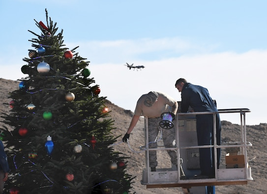 Two Creech Air Force Base members decorate a Christmas tree Dec. 2, 2017, at Creech AFB, Nev. Diamond Resorts International donated the tree and decorations as a thank you to Creech service members and their families. (U.S. Air Force photo/Senior Airman Christian Clausen)