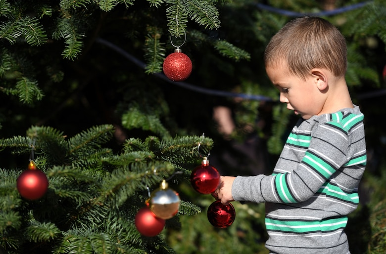 A child decorates the first Creech Air Force Base Christmas tree Dec. 2, 2017, at Creech AFB, Nev. Creech hosted its first tree-lighting ceremony to celebrate in conjunction with Creech's Children Holiday Party. (U.S. Air Force photo/Senior Airman Christian Clausen)