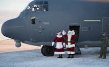 Mr. and Mrs. Santa Claus, travelling with Operation Santa Claus, de-board an HC-130J Combat King II aircraft from the 211th Rescue Squadron, Alaska Air National Guard, after landing in St. Michael, Alaska, Dec. 5, 2017. Operation Santa Claus is an Alaska National Guard annual community outreach program that provides Christmas gifts, books, backpacks filled with school supplies, fresh fruit and sundaes to youngsters in rural communities. (U.S. Army National Guard photo by 2nd Lt. Marisa Lindsay)