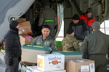 Alaska Air National Guardsman Lt. Col. Eric Budd, commander of the 211th Rescue Squadron, and other National Guard and community volunteers unload an HC-130J Combat King II aircraft in St. Michael, Alaska, on Dec. 5, 2017. Operation Santa Claus is an Alaska National Guard annual community outreach program that provides Christmas gifts, books, school supplies, fresh fruit and sundaes to youngsters in rural communities. (U.S. Army National Guard photo by Staff Sgt. Balinda O'Neal Dresel)