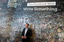 Former U.S. Secretary of Defense Ashton Carter stands in front of the Facebook wall during his visit to the company