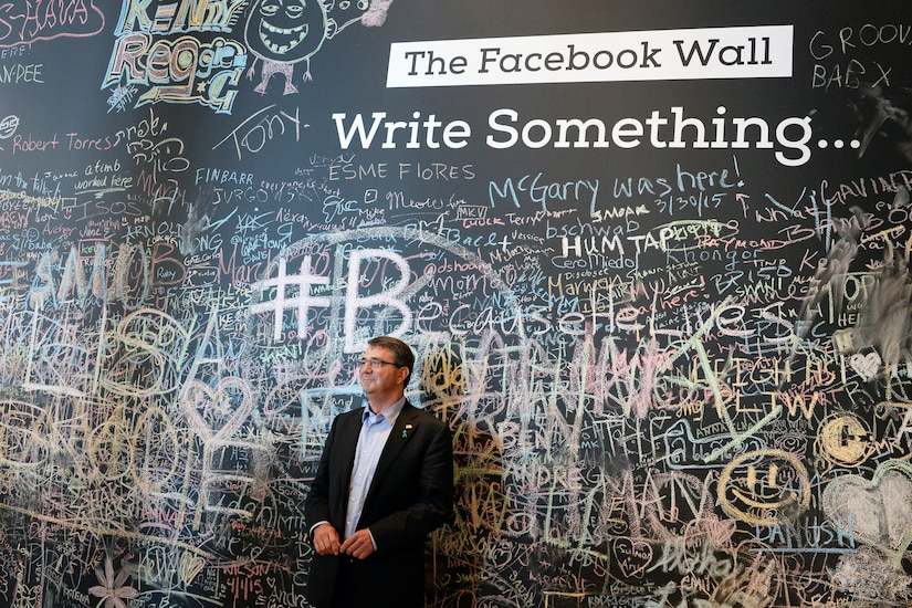 Former U.S. Secretary of Defense Ashton Carter stands in front of the Facebook wall during his visit to the company headquarters in 2014. Before the visit, the Defense Secretary unveiled DOD's cyber strategy at Stanford University.