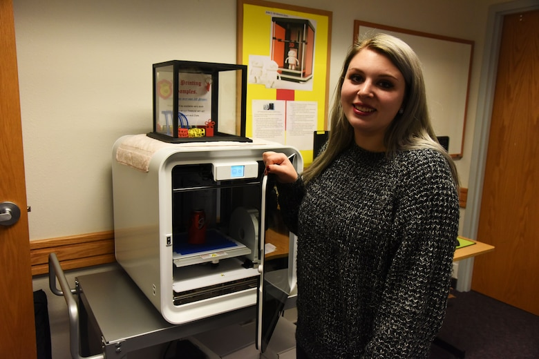 Teia Storm, 341st Force Support Squadron library aide, poses for a photo in front of a 3-D printer Dec. 6, 2017, at Arden G. Hill Memorial Library, Malmstrom Air Force Base, Mont.