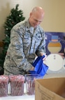 "Col. Michael Manion, 55th Wing commander, helps assemble bags filled with food, treats, and thank you's at the Bellevue Volunteer Fire Department hall in Bellevue, Neb. Dec. 5, 2017 as part of ""Operation Holiday Cheer."""