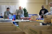 "Col. Michael Manion, 55th Wing commander, and 55th Wing Command Chief Master Sgt. Brian Kruzelnick help assemble bags filled with food, treats, and thank you' s at the Bellevue Volunteer Fire Department hall in Bellevue, Neb. Dec. 5, 2017 as part of ""Operation Holiday Cheer."""