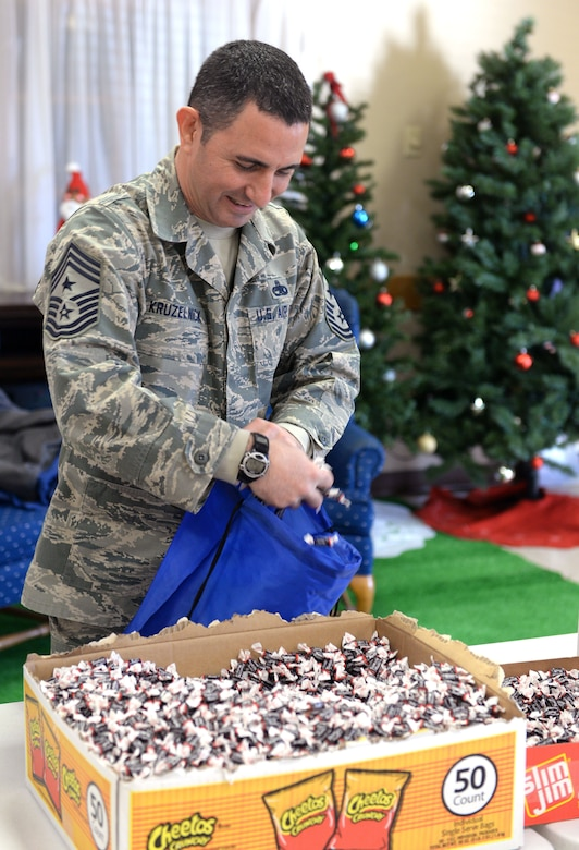 "Command Chief Master Sgt. Brian Kruzelnick, 55th Wing command chief, helps assemble bags filled with food, treats, and thank you' s at the Bellevue Volunteer Fire Department hall in Bellevue, Neb. Dec. 5, 2017 as part of ""Operation Holiday Cheer."""