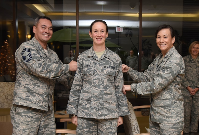 Chief Master Sgt. Joe Dittman, 81st Medical Group medical technician functional manager, and Col. Debra Lovette, 81st Training Wing commander, present Senior Master Sgt. Jolynn Kari, 81st medical Support Squadron functional manager, with chief master sergeant stripes at the Keesler Medical Center Dec. 7, 2017, on Keesler Air Force Base, Mississippi. Keesler senior NCOs were recognized for their selection to join the top one percent of the Air Force's enlisted force. (U.S. Air Force photo by Kemberly Groue)