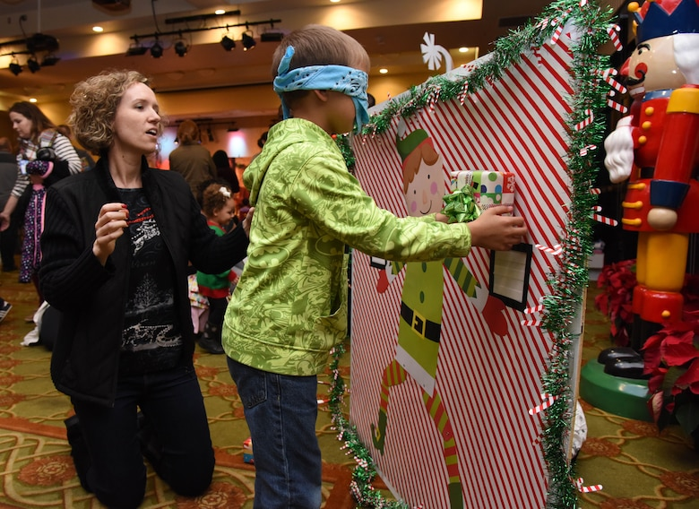 First Lt. Davina Armbruster, 81st Inpatient Operation Squadron labor and delivery nurse, assists Ryan Hoskins, son of 1st Lt. Nina Hoskins, 81st Surgical Operations Squadron operating room nurse, with a festive game during Keesler's annual Christmas celebration at the Bay Breeze Event Center Dec. 7, 2017, on Keesler Air Force Base, Mississippi. The event, hosted by Outdoor Recreation, included cookie and ornament decorating, games and visits with Santa. (U.S. Air Force photo by Kemberly Groue)