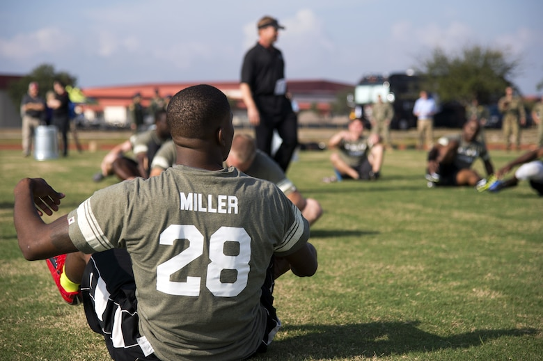 U.S. Air Force Airman 1st Class William Miller, a firefighter assigned to the 6th Civil Engineer Squadron, stretches during a football camp hosted by Jon Gruden, a Monday Night Football color analyst, at MacDill Air Force Base, Fla., Dec. 8, 2017. Miller was one of approximately 30 MacDill personnel who volunteered to participate in this event to learn football from a Super Bowl winning coach.