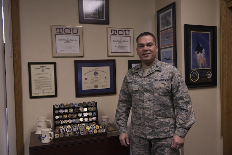 Lt. Col. Ismael Rodriguez, 366th Fighter Wing wing chaplain, stands next to his wall with his degrees, coins, and certificates received throughout his Air Force and civilian career Dec. 7, 2017, at Mountain Home Air Force Base, Idaho. This year makes a total of 20 years in the service. (U.S. Air Force photo by Senior Airman Lauren-Taylor Levin)