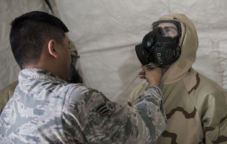 Senior Airman Co Nguyen, 92nd Civil Engineer Squadron logistics journeyman, helps an airman properly dawn a M50 gas mask during an exercise, at Fairchild Air Force Base, Washington Nov. 30, 2017. Mobility Airmen are trained to be wary of potential CBRN environments, as they can appear normal to naked eye. (U.S. Air Force photo/ Senior Airman Sean Campbell)