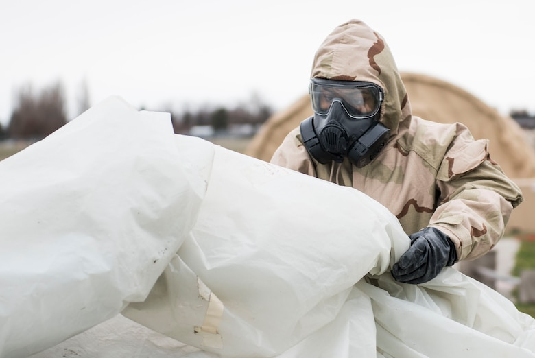 Airman 1st Class Ashley Sanchez, 92nd Communication Squadron knowledge management, demonstrates how to cover an asset in the case of a chemical attack during an exercise, at Fairchild Air Force Base, Washington Nov. 30, 2017. Environmental attacks may affect more than the Airmen themselves, as agents can remain on equipment surfaces and render them unusable. (U.S. Air Force photo/ Senior Airman Sean Campbell)