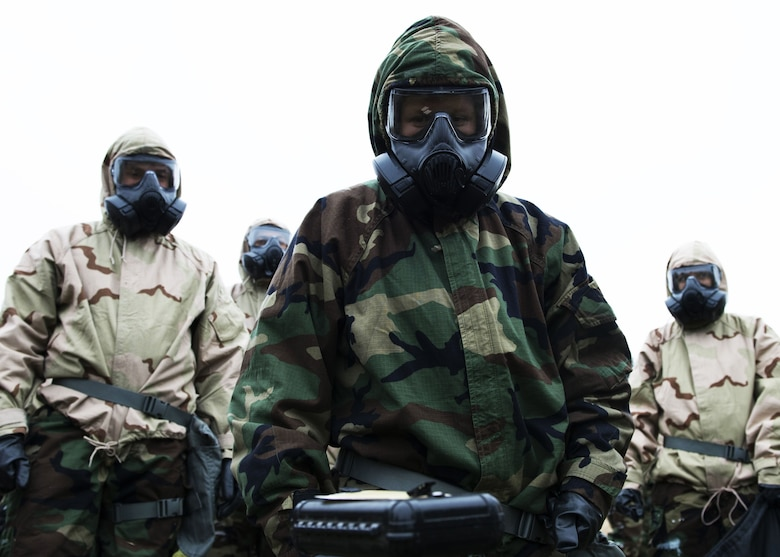 Airmen clad in full chemical warfare protective equipment analyze a post attack reconnaissance stand during an exercise at Fairchild Air Force Base, Washington, Nov. 30, 2017. PAR stands are one of many detection tools used to show evidence of harmful chemical agents. (U.S. Air Force Photo/ Senior Airman Ryan Lackey)