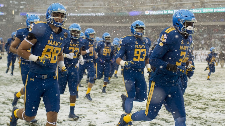 Football players run onto a snowy football field.